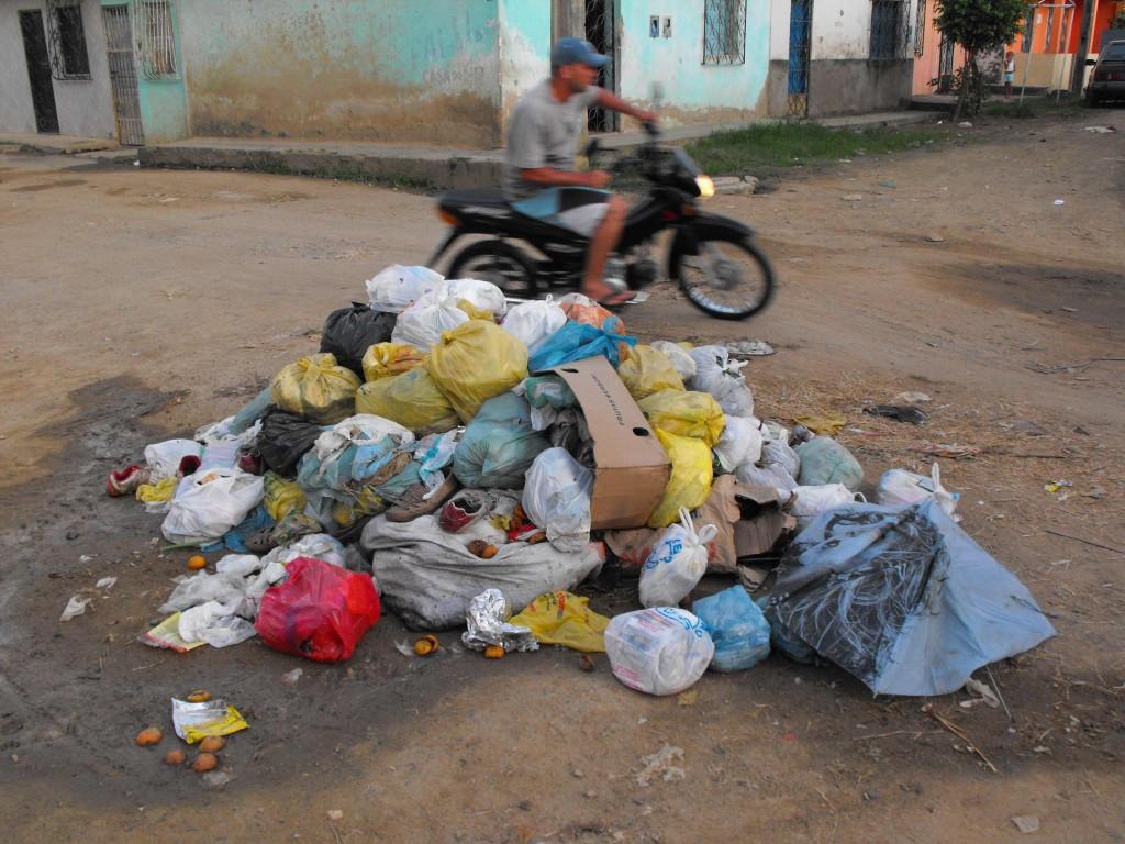 Moradores se revoltam e jogam lixo no meio da rua.
