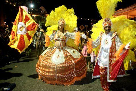 Porta-bandeira e mestre-sala anunciam escola de samba na avenida.